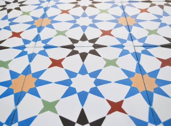 Carreaux de ciment motif étoile coloré sur le sol d'une cuisine à Paris dans le 4ème arrondissement