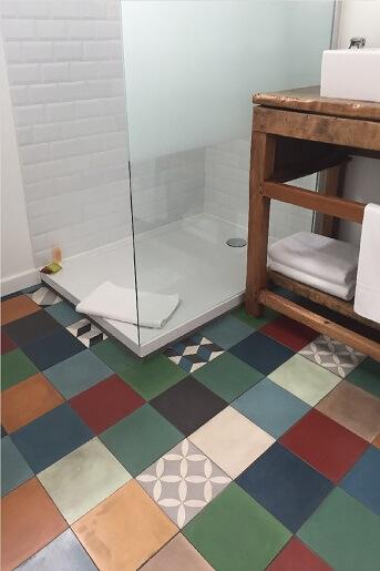 patchwork de carreaux de ciment colorés sur le sol d'une salle de bain