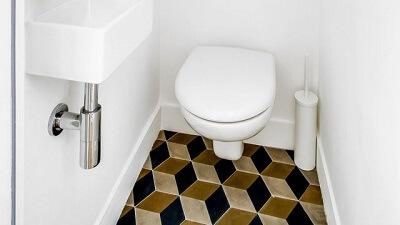carreaux de ciment hexagonaux géométriques modernes sur le sol d'un toilette