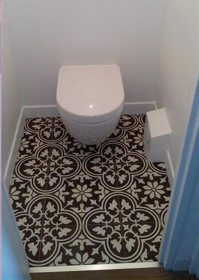 carreau de ciment floral noir et blanc sur le sol d'un toilette