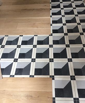 carreaux de ciment géométriques sur le sol d'une cuisine avec du parquet